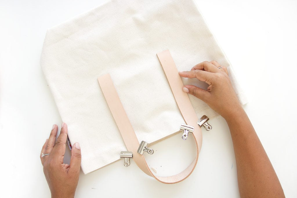 Transform a regular canvas tote bag into a DIY Leather Strap Canvas Tote Bag with the addition of leather and a few basic crafting supplies.