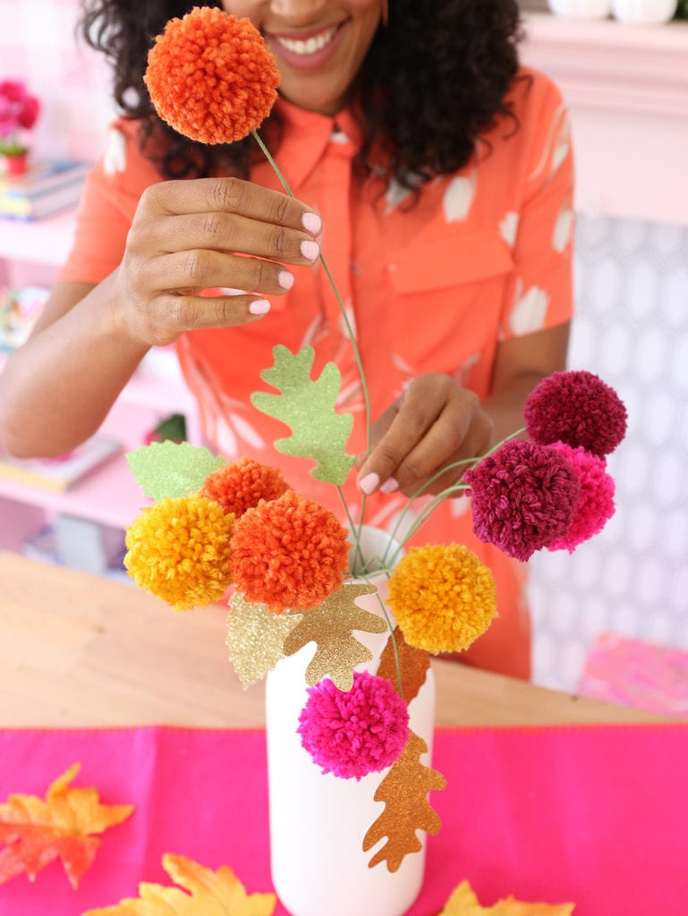 Arrange the pom pom flowers into a vase with glittery paper leaves
